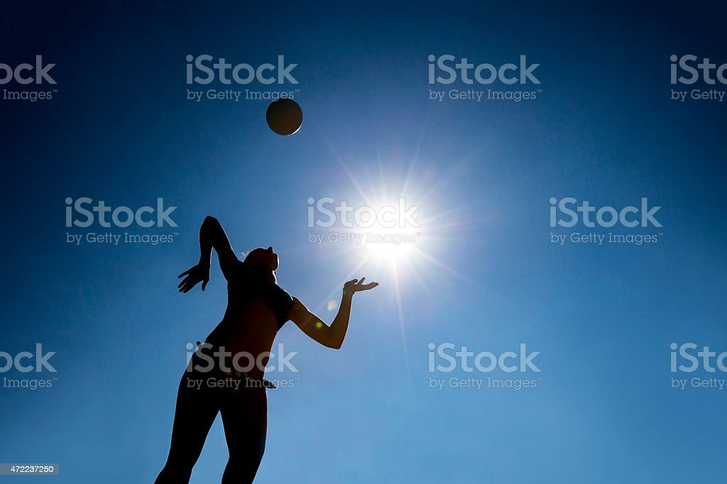 Silhouette of Volleyball Player Serving in Mid-air stock photo