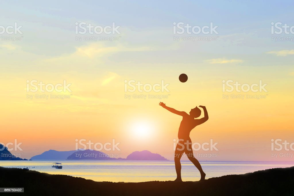 silhouette of volleyball the beach and the evening sun. stock photo