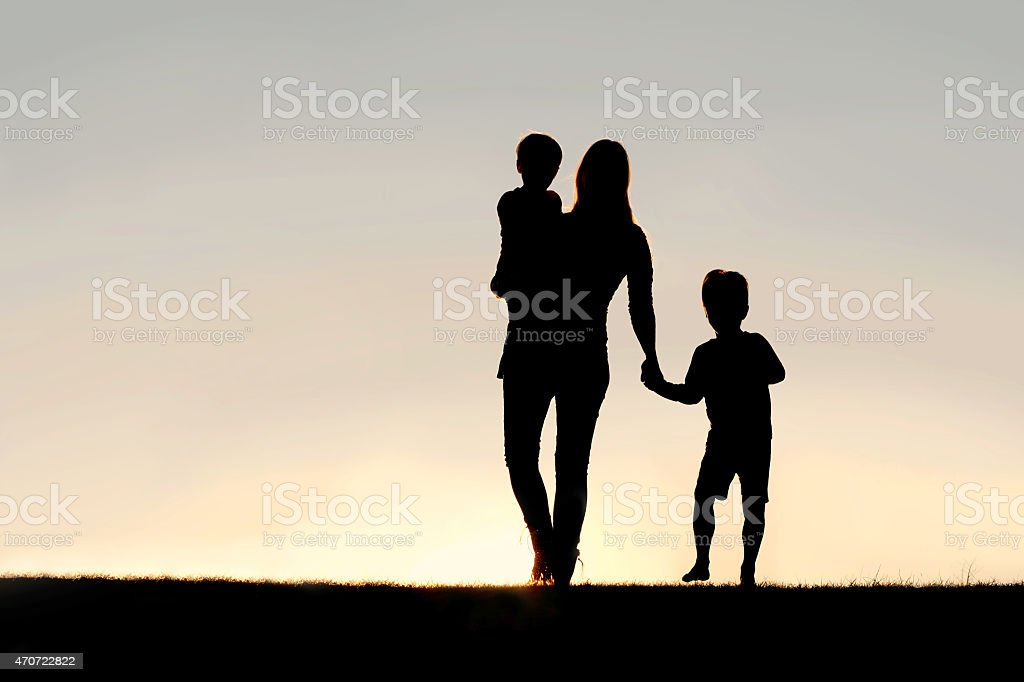 Silhouette of Walking Mother and Young Children Holding Hands at stock photo