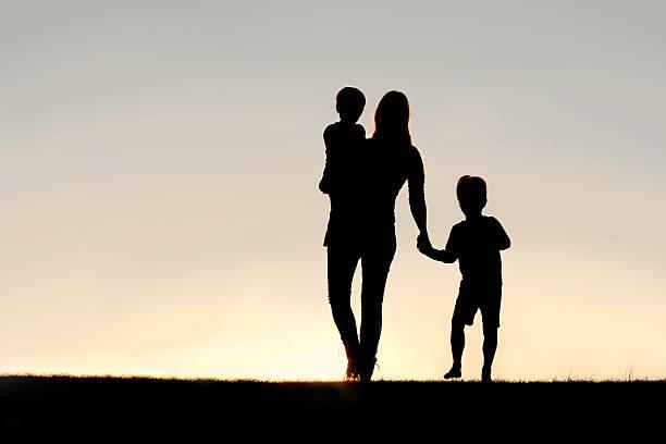 Silhouette der Walking Mutter und junge Kinder Hände halten am – Foto