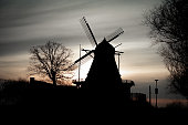 The silhouette of a windmill in Kronetorp, outside Malmö, Sweden, as the winter sun sets behind it
