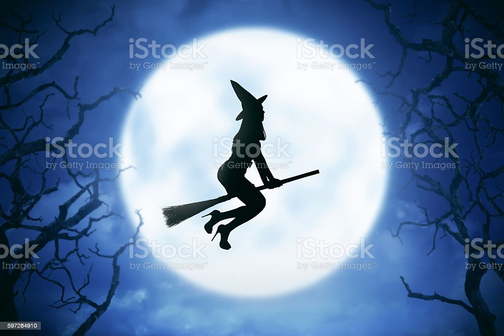 Silhouette of witch woman riding magic broom stock photo