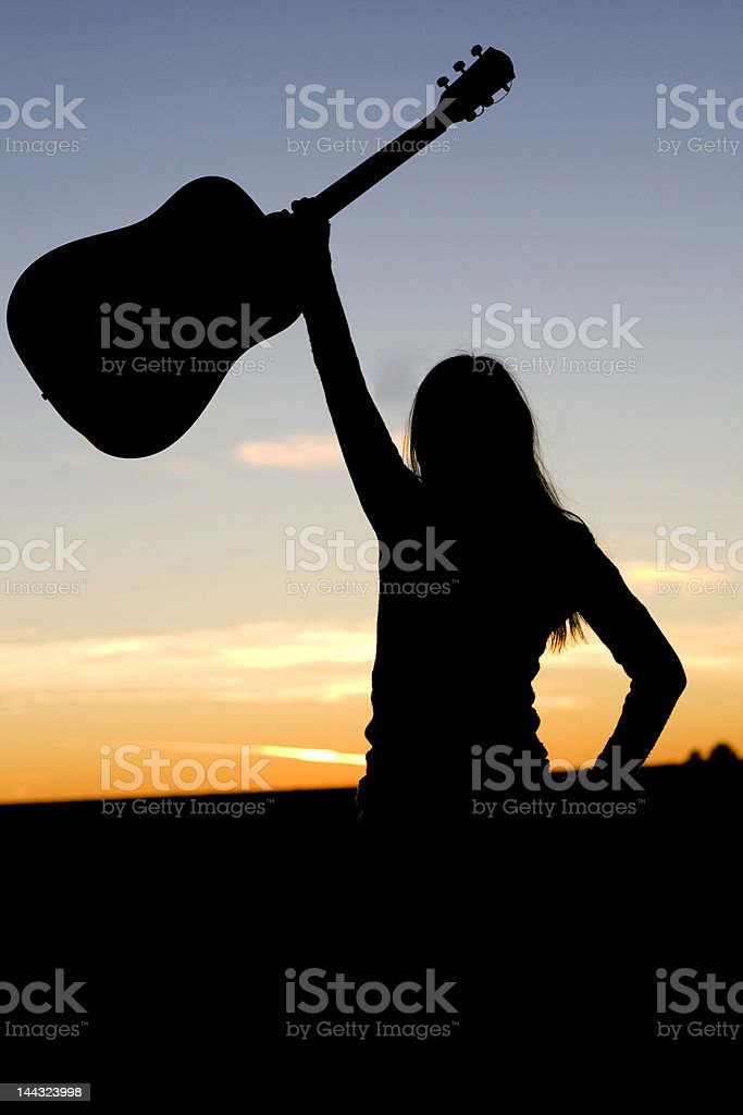 Silhouette of Woman and Her Guitar royalty-free stock photo