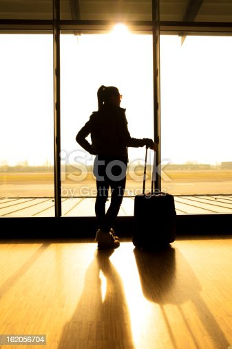 512522378 istock photo Silhouette of woman at airport with suitcase waiting for flight 162056704