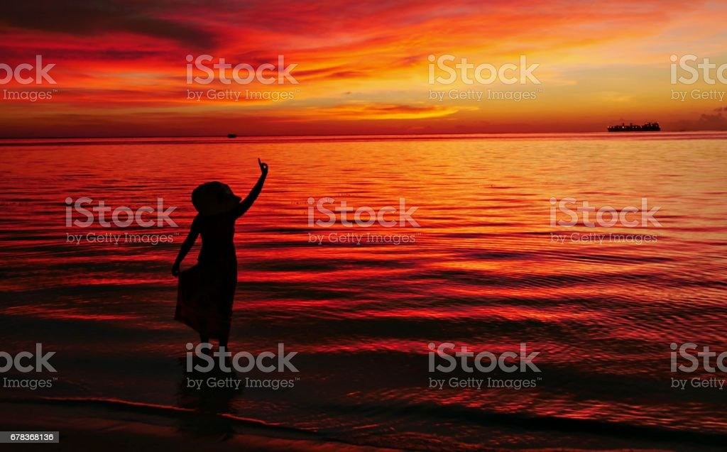 Silhouette of woman at sunset stock photo
