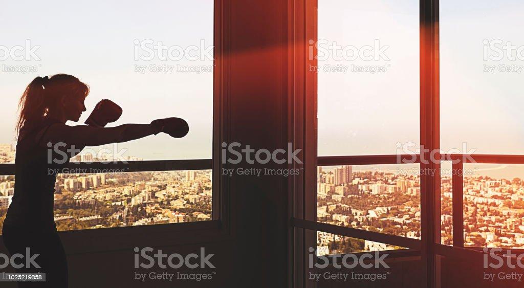 Silhueta de mulher boxe dentro de casa - foto de acervo