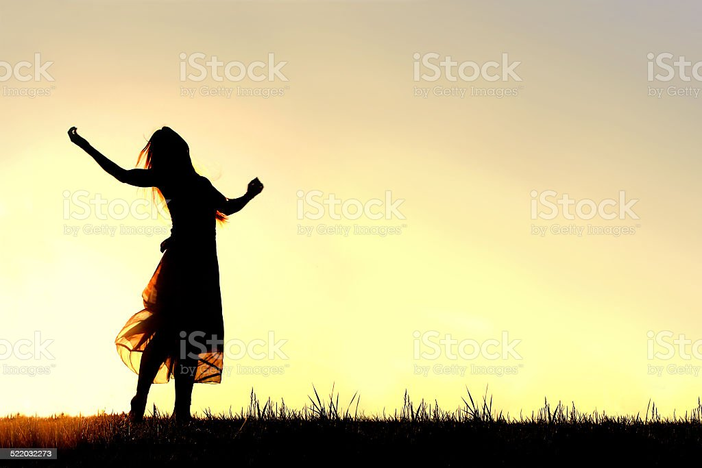 Silhouette of Woman Dancing and Praising God at Sunset stock photo