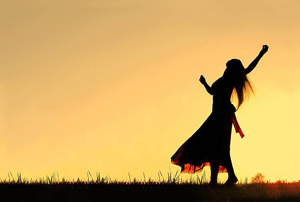 silhouette der frau tanzen und freudige feierlichkeit zu gott bei sonnenuntergang - herumwirbeln frau stock-fotos und bilder