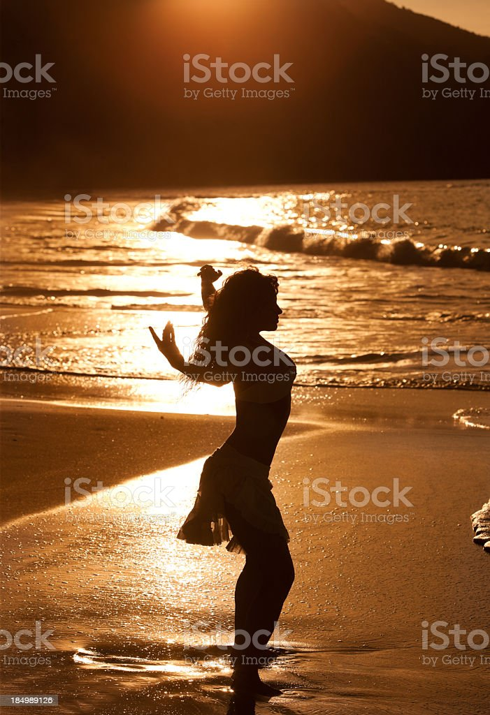 silhouette of woman dancing at the Caribbean beach during sunset stock photo