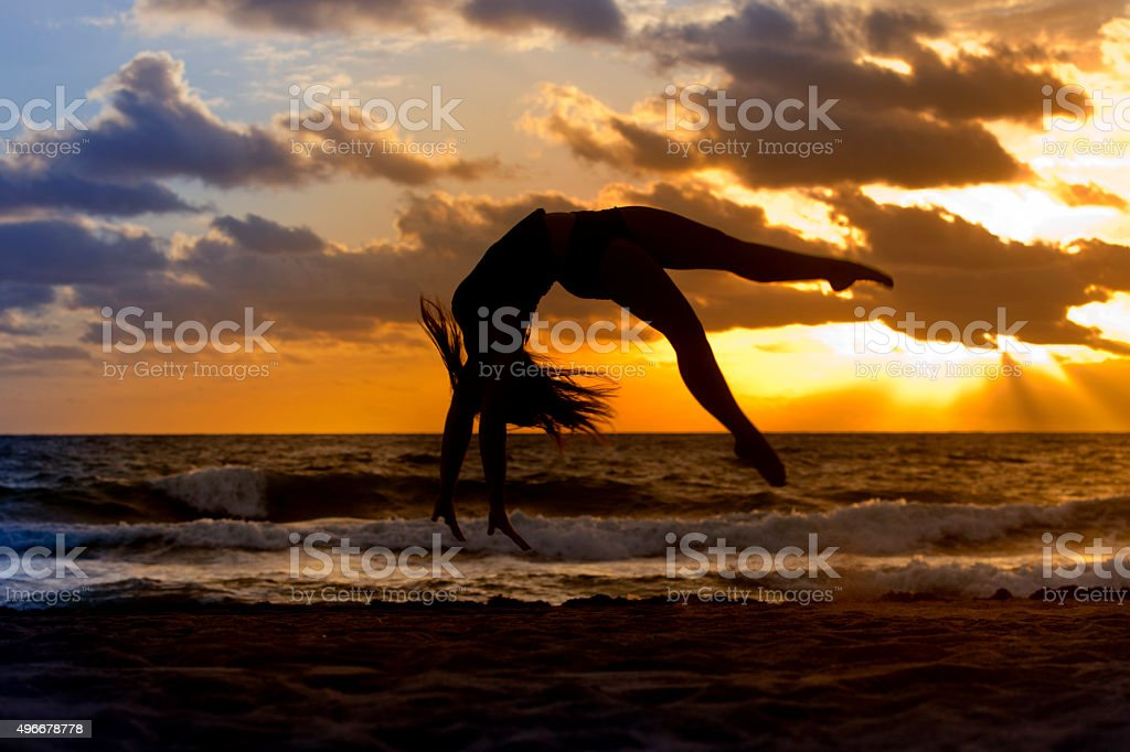 Silhouette of woman doing a back flip on a beach stock photo