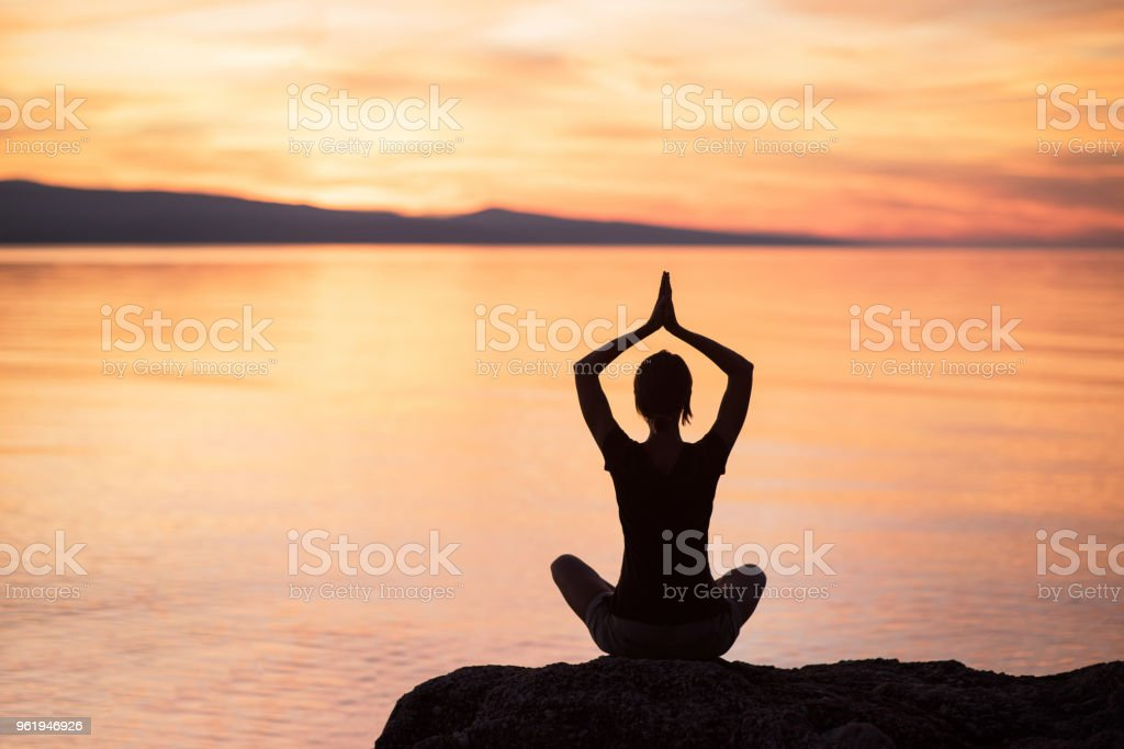 Silhouette of woman doing yoga outdoors. Meditation and harmony concept stock photo