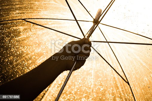 691761646istockphoto Silhouette of woman hand opening an umbrella in the rain 691761686