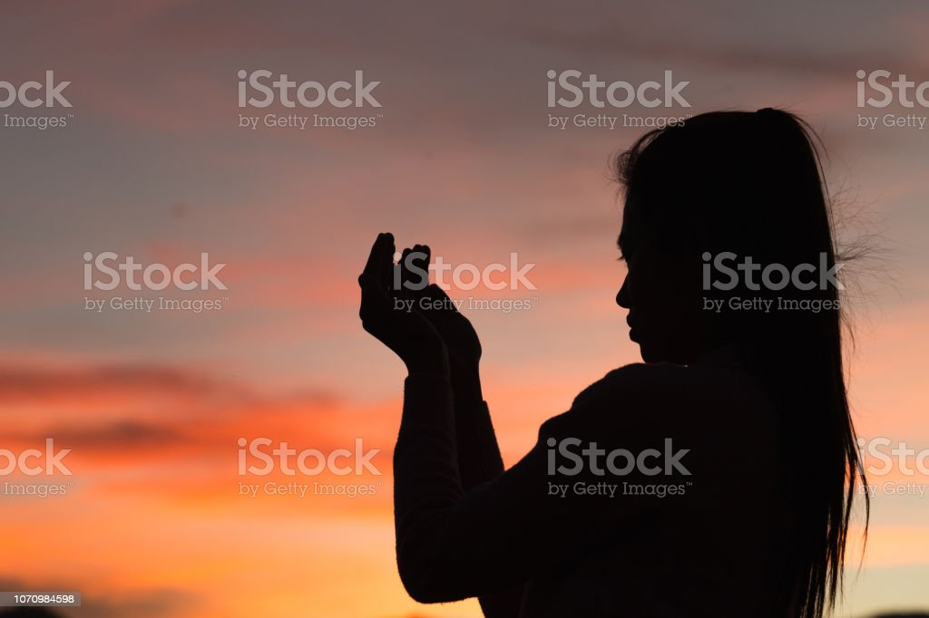 Silhouette of woman hands praying to god with the bible. Woman Pray...