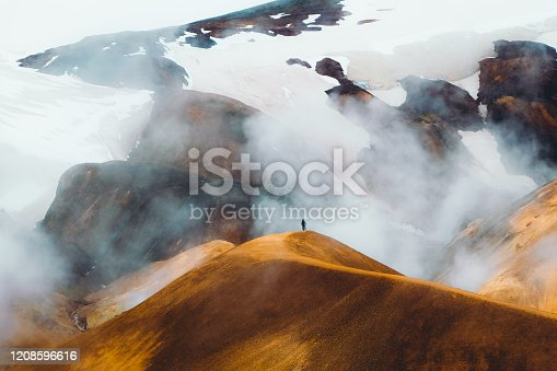Young woman tourist enjoying morning hiking at the panoramic geothermal smoking bright colorful mountain land in the wilderness of Iceland Highlands