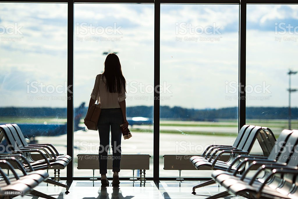 Silhouette of woman in airport lounge waiting for flight aircraft stock photo