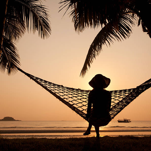 silhouette of woman in hammock woman in hammock enjoying sunset on the beach koh chang stock pictures, royalty-free photos & images