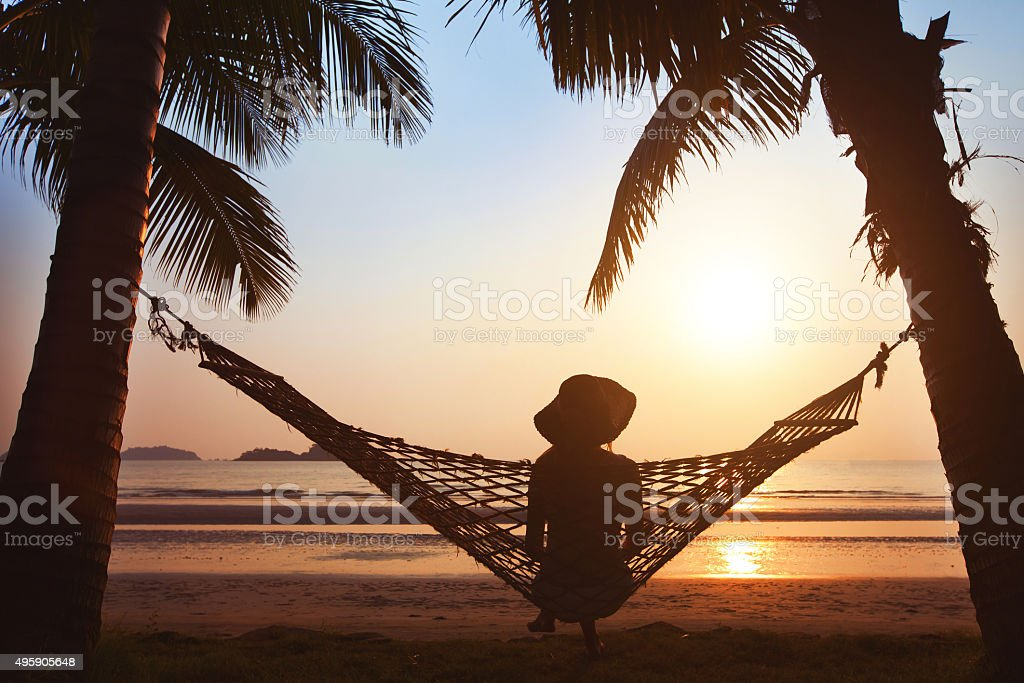silhouette of woman in hat woman relaxing in hammock at sunset on the beach 2015 Stock Photo