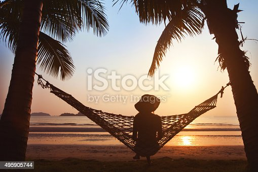 woman relaxing in hammock at sunset on the beach
