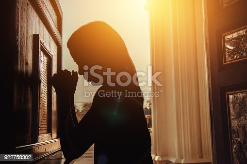 silhouette of woman kneeling and praying in modern church at sunset time