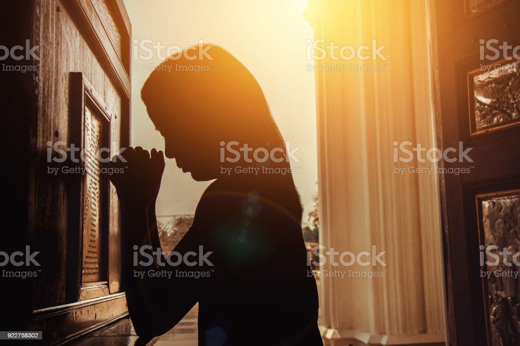silhouette de femme à genoux et de prier dans l'église moderne au moment du coucher du soleil - Photo