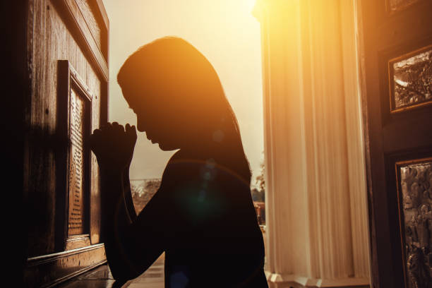 silhouette of woman kneeling and praying in modern church at sunset time stock photo