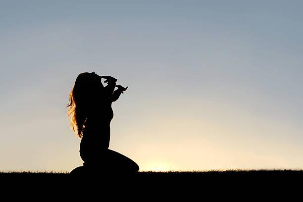 silhouette di donna in ginocchio in preghiera e resa - molla foto e immagini stock