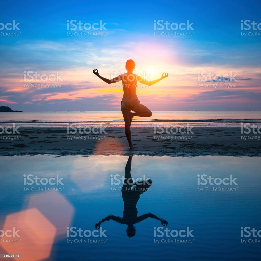 Silhouette of woman meditating on the sea beach. stock photo