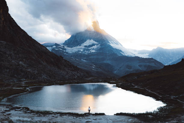 Silhouette of woman meets sunset near beautiful mountain lake with Matterhorn view in Swiss Alps stock photo