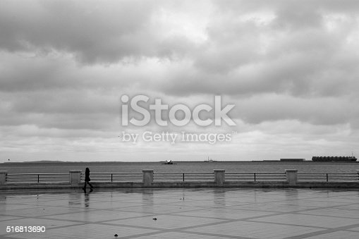 A lone figure walks on the seafront in inclement weather in Azerbaijan's capital city