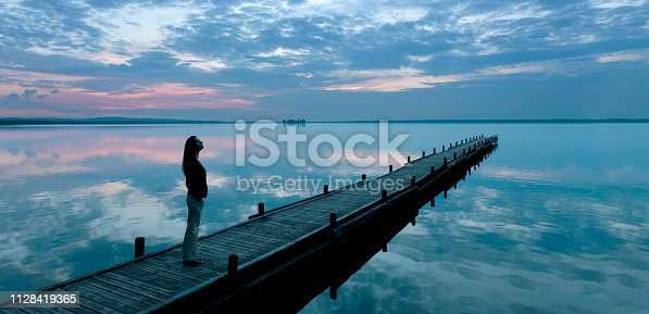 619670604 istock photo Silhouette of woman on jetty at lake watching majestic cloudscape at dusk 1128419365
