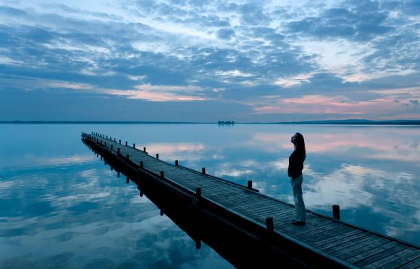 Silhouette of woman on jetty watching majestic blue twilight cloudscape reflection on lake stock photo
