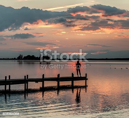 istock Silhouette of woman on lakeside jetty looking at dusk cloudscape 628364058