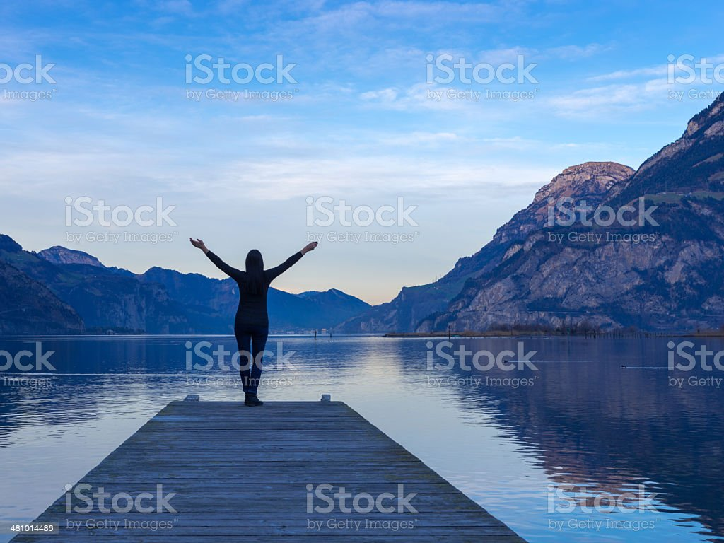 Silhouette of Woman on Lakeside Jetty stock photo