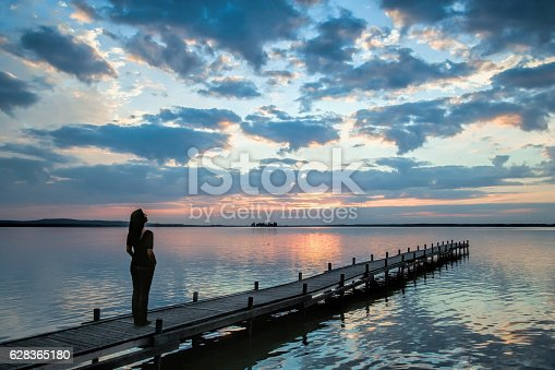 istock Silhouette of woman on lakeside jetty watching sunset cloudscape 628365180
