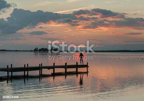 619670604 istock photo Silhouette of woman on lakeside jetty with majestic sunset cloudscape 509624456