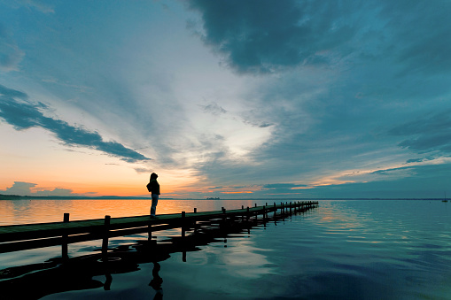 Young woman standing lakeside on jetty having a look at magical cloudscape and sunset colors.