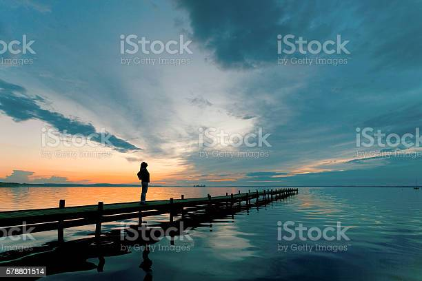 Photo of Silhouette of Woman on Lakeside Jetty with majestic Sunset Cloudscape