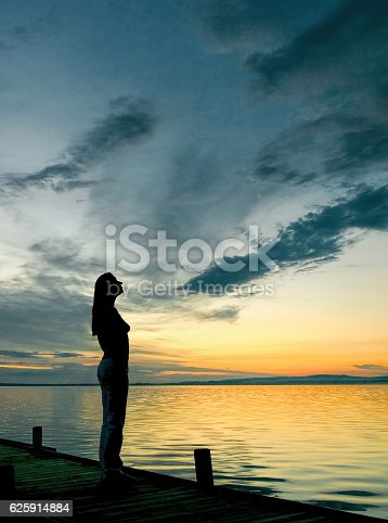619670604 istock photo Silhouette of Woman on Lakeside Jetty with majestic Sunset Cloudscape 625914884