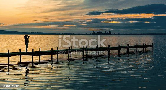 619670604 istock photo Silhouette of Woman on Lakeside Jetty with majestic Sunset Cloudscape 625915012