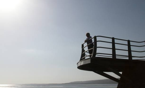 Silhouette of woman on viewing platform at beach stock photo