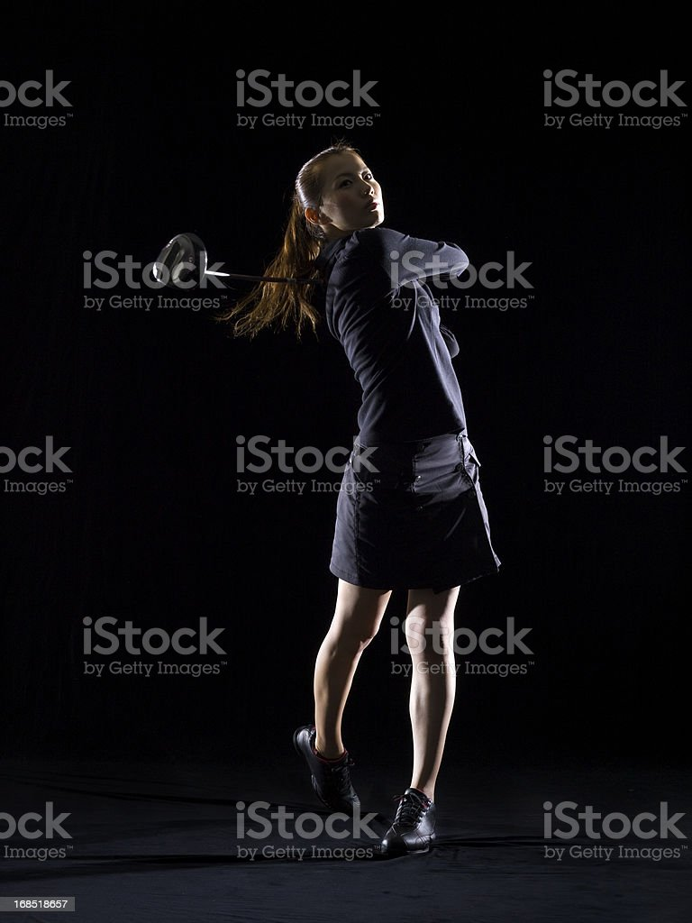 Silhouette of woman playing golf stock photo