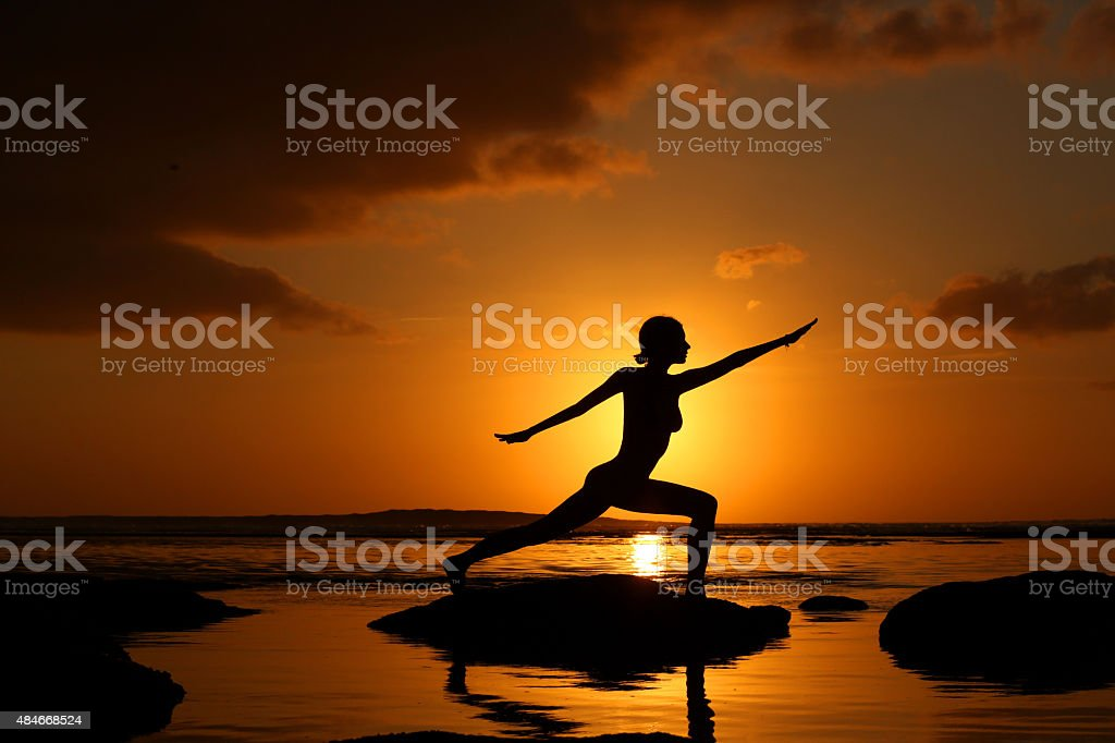 Silhouette of woman practicing yoga during sunset at the seaside stock photo