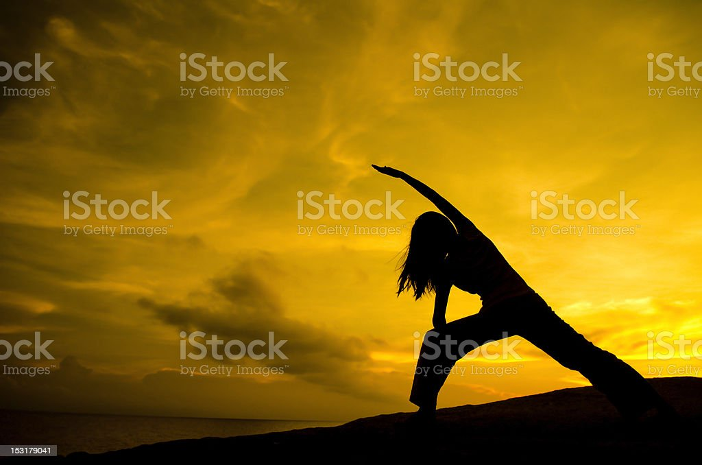 Silhouette of Woman Practicing Yoga stock photo