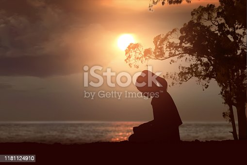 Silhouette of woman read the bible on the beach with a sunset sky background