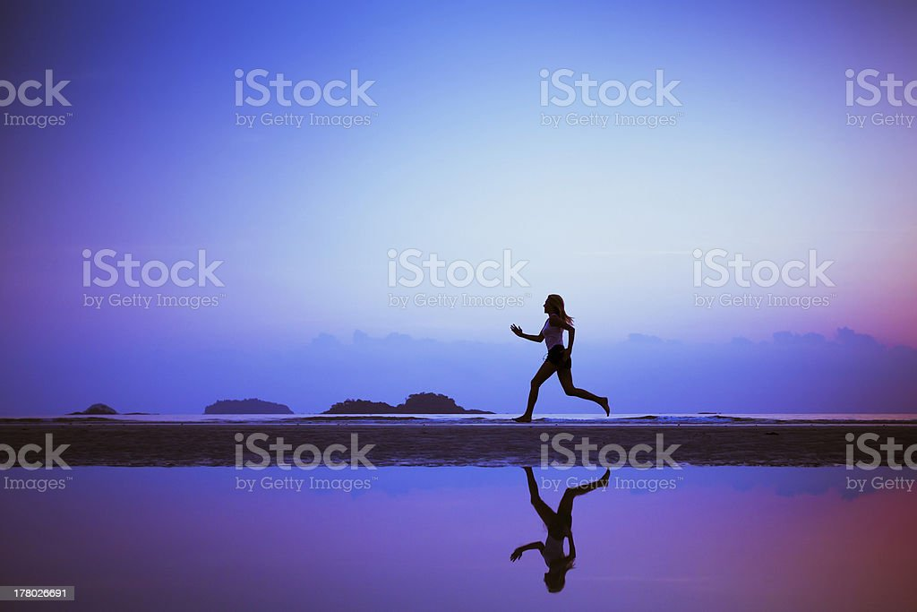 Silhouette of woman running next to body of water at sunrise stock photo