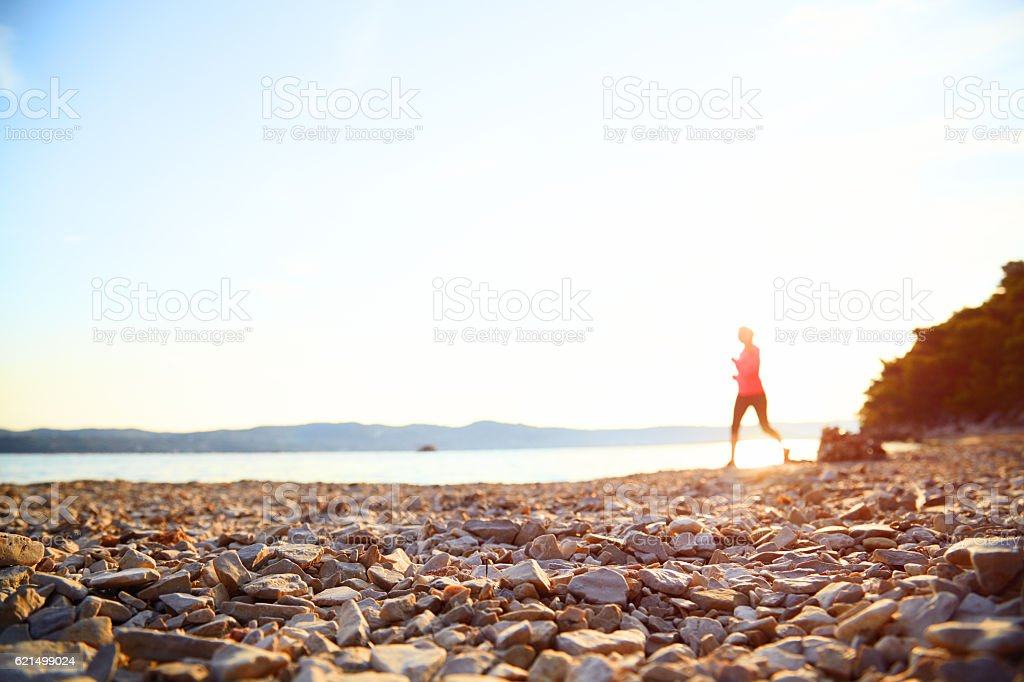 Silhouette of woman running on beach near sea at sunrise. foto stock royalty-free