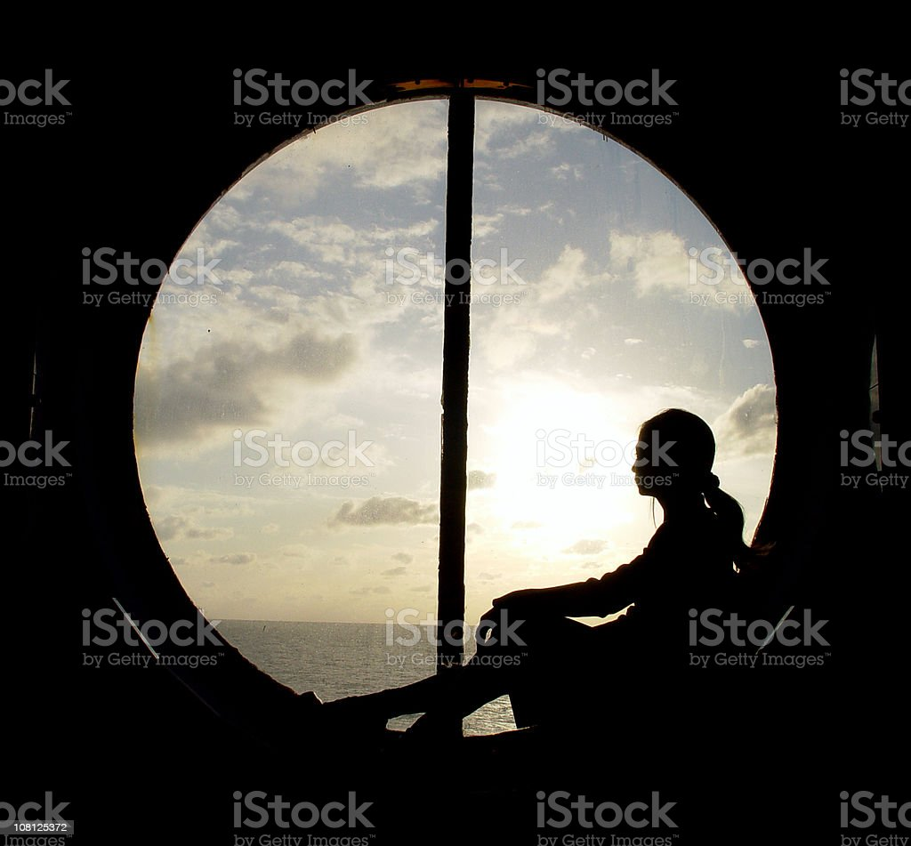 Silhouette of Woman Sitting in Ship's Porthole Window stock photo