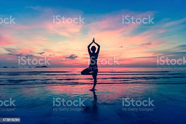 Silhouette Of Woman Standing At Yoga Pose On The Beach Stock Photo - Download Image Now
