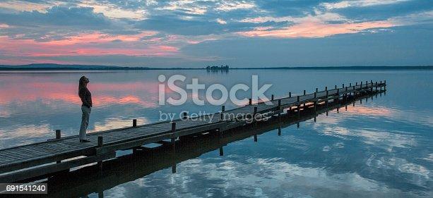 istock Silhouette of woman standing on jetty at lake watching idyllic scenics at dusk 691541240