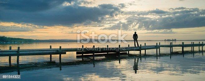 619670604 istock photo Silhouette of woman standing on jetty at lake watching idyllic scenics with majestic cloudscape 691544322